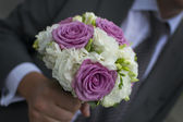 An elegant bouquet or bunch of flowers in a hand of groom or man — Stock Photo
