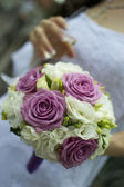 An elegant hand-tied bouquet of flowers in the hand of a bride. Shallow depth of field — Stock Photo