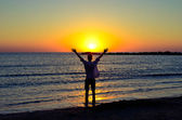 Happy man welcoming the sunrise on the beach — Stock Photo