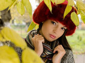 Beautiful woman hiding behind autumn leaves — Stock Photo