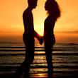 Couple enjoying their time at the sunrise on the beach — Stock Photo