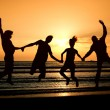 Group of happy parting on beach at sunrise — Stock Photo #27246763