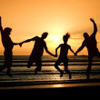 Stock Photo: Group of happy parting on beach at sunrise