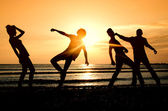 Group of happy parting on the beach at sunrise — Stock Photo