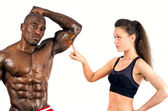 Beautiful woman impressed by the muscles of a bodybuilder — Stock Photo