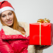 Beautiful red hair woman holding a big Christmas present. Girl in red with Santa hat smiling — Stock Photo #35126469