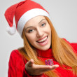 Crisis Christmas. Beautiful red hair woman holding a small Christmas present. Girl in red with Santa hat looking down smiling — Stock Photo