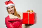 Beautiful red hair woman holding a big Christmas present. Girl in red with Santa hat smiling — Stock Photo