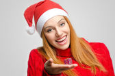 Crisis Christmas. Beautiful red hair woman holding a small Christmas present. Girl in red with Santa hat looking down smiling — Stock fotografie