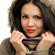Sexy young brunette girl with red lips in autumn. Portrait of a young attractive woman wearing a sweater with faux fur hood  — Stock Photo