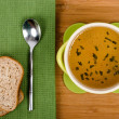 A bowl of hot organic soup on a table with a spoon and bread just ready to be eaten — Stock Photo