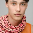 Portrait of an innocent handsome man posing fashion with colored scarf. Young guy with cool messy hairstyle — Stok fotoğraf