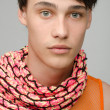 Portrait of an innocent handsome man posing fashion with colored scarf. Young guy with cool messy hairstyle — Stock Photo