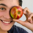 Beautiful man smiling and holding a red apple promoting a healthy life  — Stock Photo