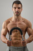 Bodybuilder training with a bendy bar. Strong man with perfect abs, pecs shoulders,biceps, triceps. Isolated on white background — Stock Photo