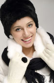 Portrait of a beautiful woman with big blue eyes and red lips smiling and wearing a black hat and white fur coat — Stock Photo
