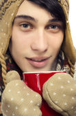 Portrait of a beautiful man wearing sweater, gloves, scarf and a hat, dressed for winter cold and drinking a hot cup of tea — Stock Photo