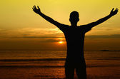 Man welcoming the sun, sunrise on the beach — Stock Photo