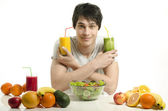 Happy man choosing between orange juice and green smoothie. Cheerful young man eating healthy salad and fruits. Isolated on white. — Stock Photo