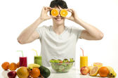 Happy man holding in front of his eyes oranges. Cheerful young man eating healthy salad, fruits , orange juice and green smoothie. — Stock Photo