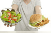 Man hands offering you a salad and a hamburger. Unrecognizable person holding in front a bowl of salad and a big burger. Choosing between good healthy food and bad unhealthy food. — Stock Photo