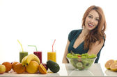Happy woman having a table full of organic food,juices  and smoothie. Cheerful young woman eating healthy salad and fruits. Isolated on white. — Stock Photo