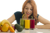 Happy woman holding in front of her three different smoothie.. Cheerful young woman eating healthy salad, fruits , orange juice and green smoothie — Stock Photo