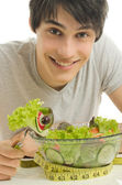 Man measuring his biceps with a centimeter while eating organic healthy salad for a perfect diet. Green food for a healty life — Stock Photo