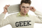 Geek playing video games with a keyboard, gamer wearing eyeglasses — Stock Photo