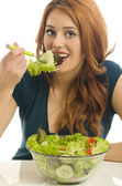 Happy woman eating organic salad. Woman keeping a diet with green salad. Close up on a young woman eyes holding a bowl of organic salad, eating healthy — Stock Photo