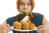 Woman with a centimeter on her mouth unable to eat all the sweets and sugar, lots of cookies on a plate — Stock Photo