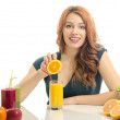 Woman squeezing and orange and preparing an organic juice. Happy woman having a table full of organic food,juices and smoothie. Cheerful young woman eating healthy salad and fruits. Isolated on white. — Foto Stock