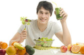 Happy man having a table full of organic food,juices and smoothie. Cheerful young man eating healthy salad and fruits. Isolated on white — Foto Stock