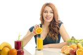 Woman squeezing and orange and preparing an organic juice. Happy woman having a table full of organic food,juices and smoothie. Cheerful young woman eating healthy salad and fruits. Isolated on white. — Stock Photo