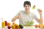 Happy man having a table full of organic food,juices and smoothie. Cheerful young man eating healthy salad and fruits. Isolated on white. — Stock Photo