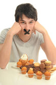Homem apaixonado por doces, doces, chocolate e açúcar, mas tentando conter de comer — Fotografia Stock