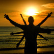 Man welcoming the sun, sunrise on the beach, multiple hands — Stock Photo