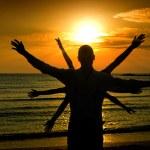 Man welcoming the sun, sunrise on the beach, multiple hands — Stock Photo