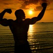 Silhouette of bodybuilder posing at the sunrise on the beach, training in the morning, strong man showing his muscles — Stock Photo #43764273