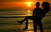Couple enjoying their time at the sunrise on the beach,man holding in his arms a woman in a romantic scene — Stock Photo