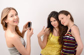 One blonde and two brunette women having fun, blonde woman photographing and smiling a couple of brunette women — Stock Photo
