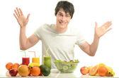 Mutlu bir adam bir masa dolu organik gıda, meyve suları ve güler yüzlü olması. yeme sağlıklı salata ve meyve neşeli bir genç adam. beyaz izole. — Stok fotoğraf