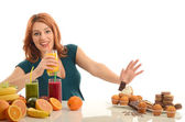 Woman choosing between fruits, smoothie and organic healthy food against sweets, sugar, lots of candies, unhealthy food — Stock Photo