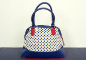 Navy blue polka dots purse on a dots surface. — Stock Photo