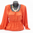 Orange blouse on mannequin with matching accessories. Elegant blouse on tailor's dummy with matching colorful necklace — Stock Photo #50026827