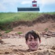 Stock Photo: Fun at beach - boy buried in sand