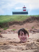 Fun at the beach - boy buried in the sand — Stock Photo