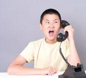 Teenage boy on the telephone screaming — Stock Photo