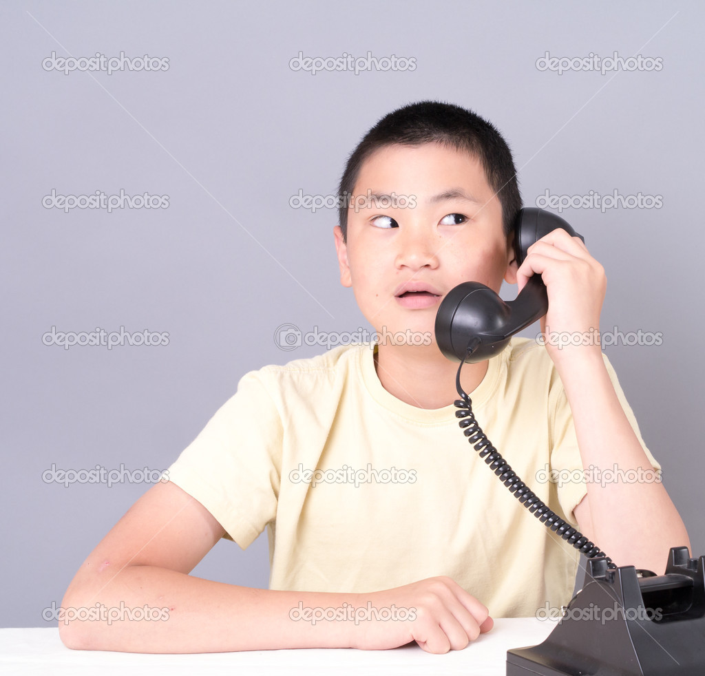 An Asian teenager with a funny expression listening on the telephone. — Stock Photo #12456885