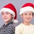 Couple of Young Teens in Santa Claus Hats — Stock Photo